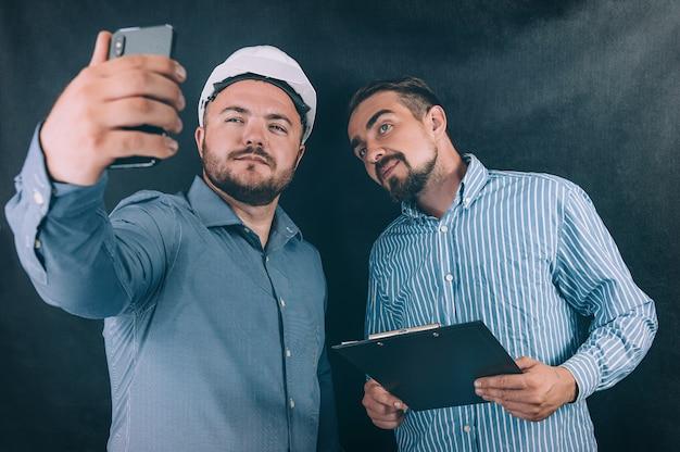 Deux hommes dans un casque de chantier prennent un selfie avec un document à la main sur un espace sombre.