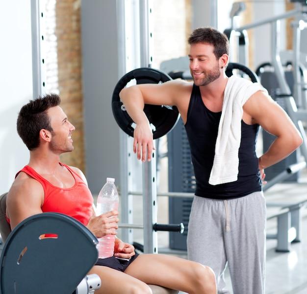 Deux hommes dans une salle de sport détendue après le fitness