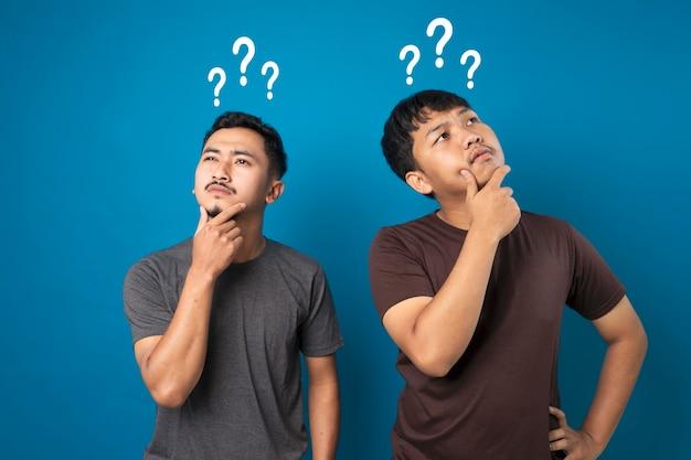 Deux hommes debout dans une pose réfléchie tenant le menton et des points d'interrogation au-dessus de leur tête