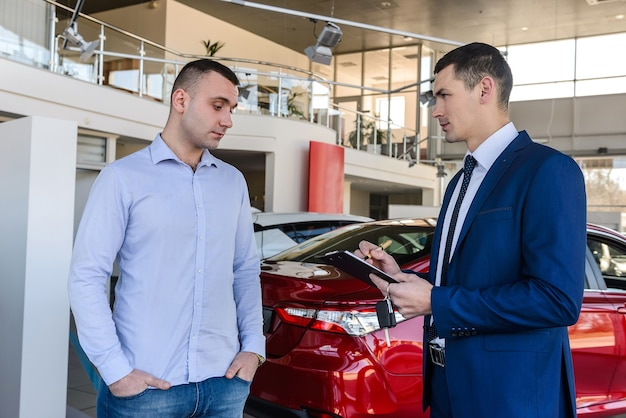 Deux hommes debout dans la salle d'exposition près de la voiture