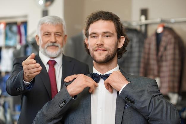 Deux hommes élégants atractifs heureux choisissant des vêtements pour une occasion spéciale.