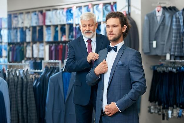 Deux hommes élégants choisissant des costumes en magasin.