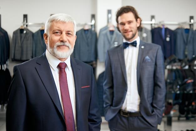 Deux hommes élégants en costumes élégants en magasin.
