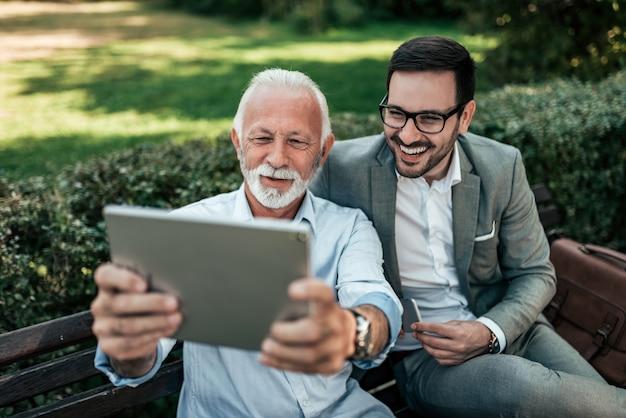 Deux hommes élégants prenant selfie sur une tablette à l'extérieur.
