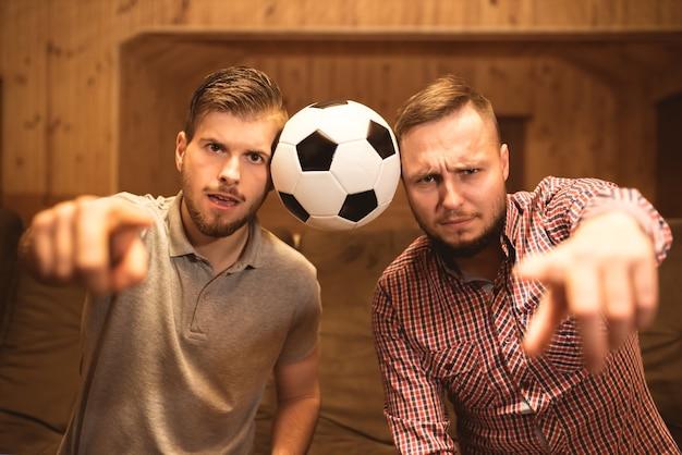 Les deux hommes avec un geste de balle à l'appareil photo