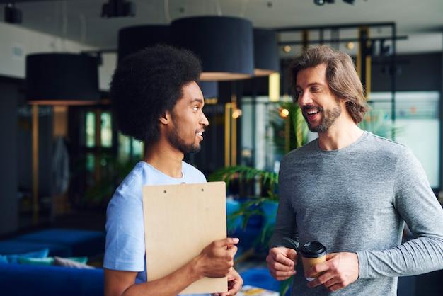 Deux hommes heureux discutant au travail