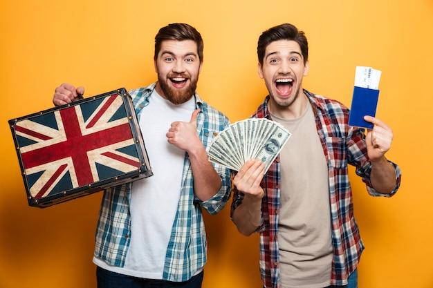 Deux hommes heureux surpris se préparent à voyager avec valise, passeport et argent sur mur jaune