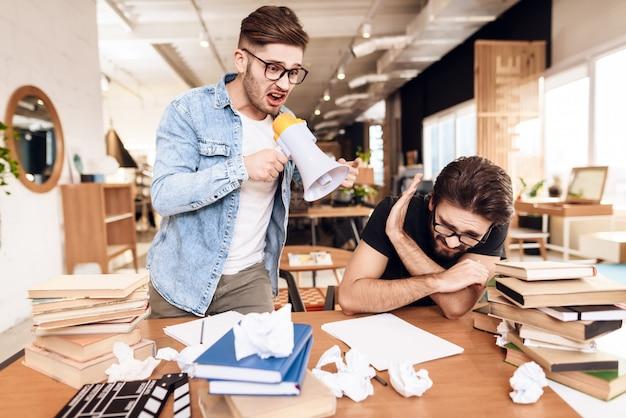 Deux hommes indépendants travaillant au bureau, entourés de livres.