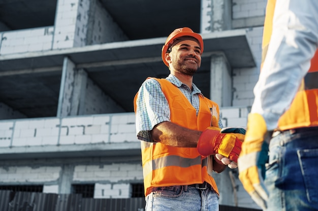 Deux hommes ingénieurs en vêtements de travail se serrant la main contre le chantier de construction, gros plan