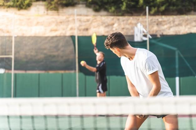 Deux hommes jouant au tennis en équipe à l'extérieur.