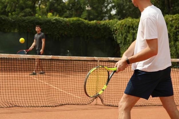 Deux hommes jouant au tennis sur terre battue