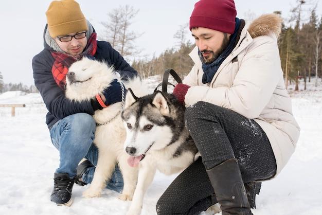 Deux hommes jouant avec des chiens en hiver