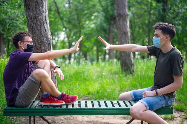 Deux hommes avec des masques médicaux parlant dans un parc