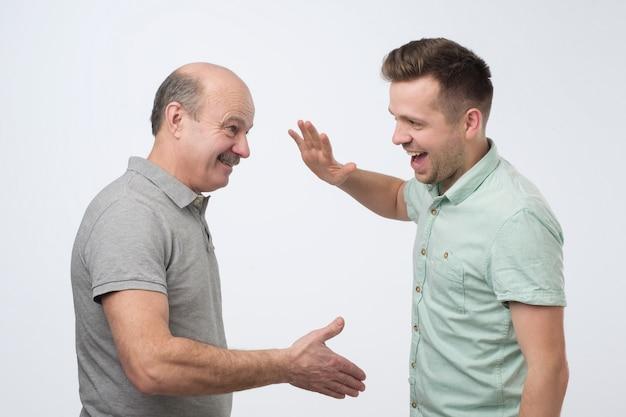 Deux hommes matures vont se serrer la main