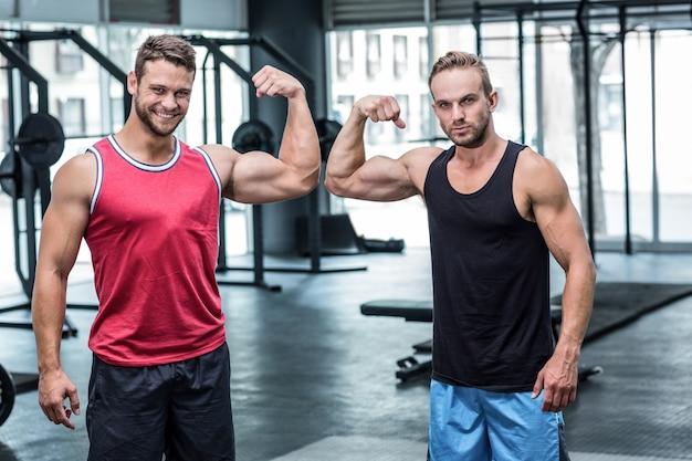 Deux hommes musclés fléchissant les biceps