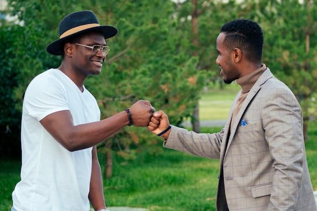 Deux hommes noirs en costumes élégants se rencontrent dans un parc d'été. des amis afro-américains, un homme d'affaires hispanique, s'embrassent en se saluant le travail d'équipe à l'extérieur. concept de transaction réussie