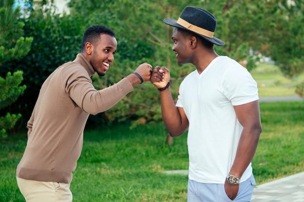 Deux hommes noirs en costumes élégants se rencontrent dans un parc d'été. amis afro-américains, homme d'affaires hispanique se saluant le travail d'équipe à l'extérieur