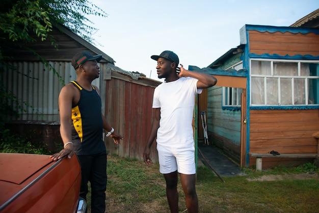 Deux hommes noirs discutent de problèmes commerciaux sur le fond d'une maison de village