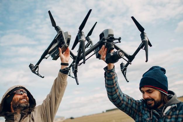 Deux hommes pilotes tenant un drone quadricoptère dans les mains à l'extérieur du champ
