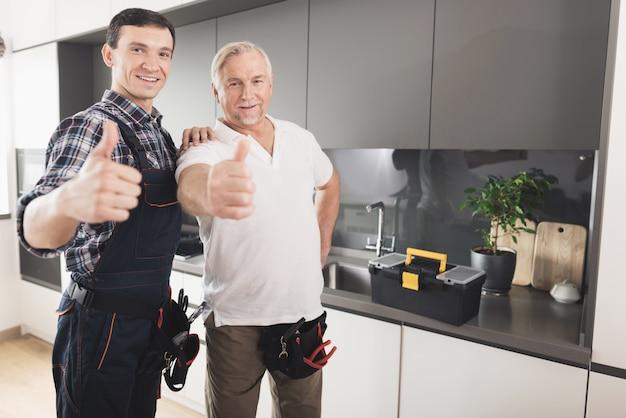 Deux hommes plombiers posant dans une cuisine moderne