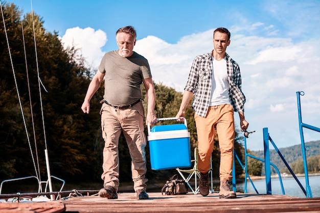 Deux hommes portant leur glacière