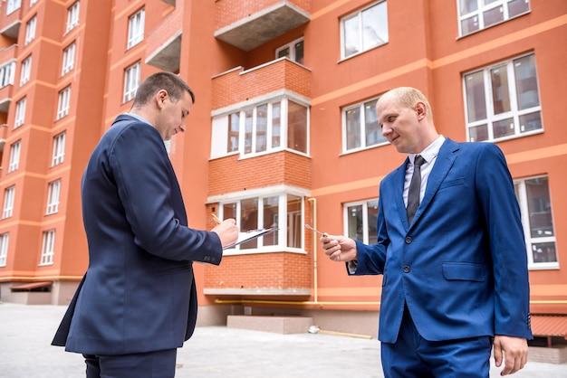 Deux hommes avec presse-papiers et clé près du nouveau bâtiment