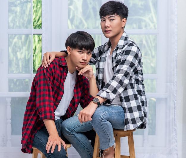 Deux hommes qui s'aiment s'embrassent et s'assoient sur une chaise.