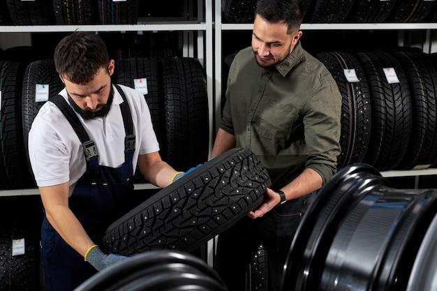 Deux hommes à la recherche de la surface des pneus auto discutant des avantages des pneus d'hiver pour l'automobile, ont parler, toucher et examiner