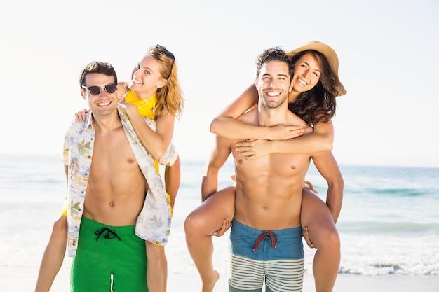 Deux hommes redonnant un piggy aux femmes sur la plage