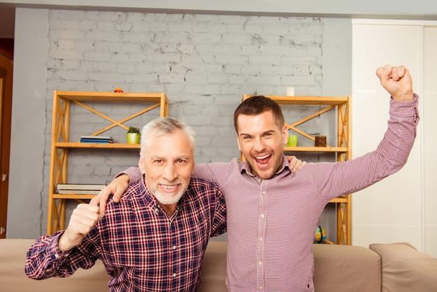 Deux hommes regardant la télévision à la maison avec les mains levées