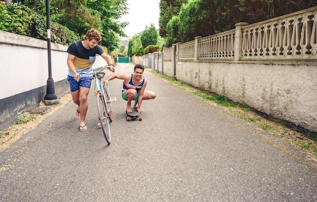 Deux hommes riant et s'amusant à faire du vélo et de la planche à roulettes dans la rue par une journée ensoleillée. concept de mode de vie jeune.