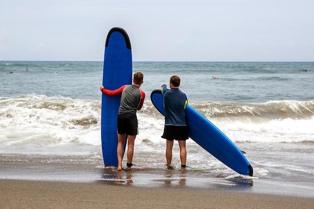 Deux hommes se mettent à l'eau pour apprendre à surfer.