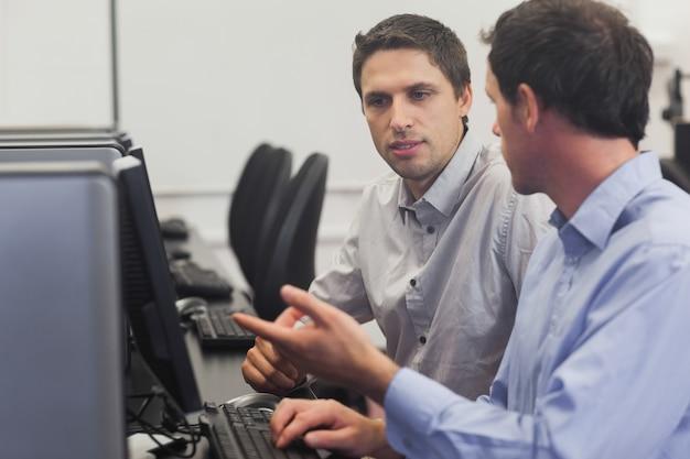 Deux hommes séduisants parlant en classe d'informatique