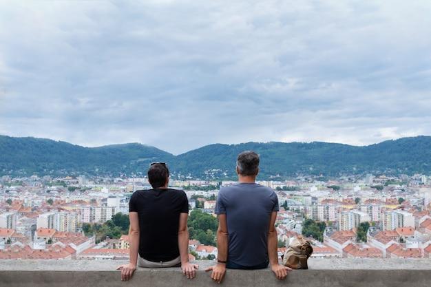 Deux hommes sont assis au bord d'un grand immeuble et regardent au loin les montagnes.