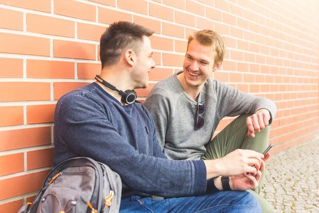 Deux hommes souriants et regardant un téléphone intelligent