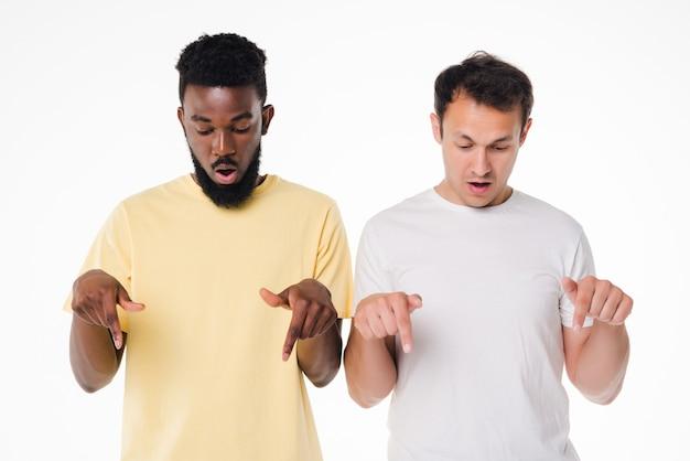 Deux hommes surpris avec des expressions faciales perplexes et effrayées pointent ensemble vers le bas, montrent quelque chose sur le sol, gardent la bouche ouverte, isolés sur un mur blanc