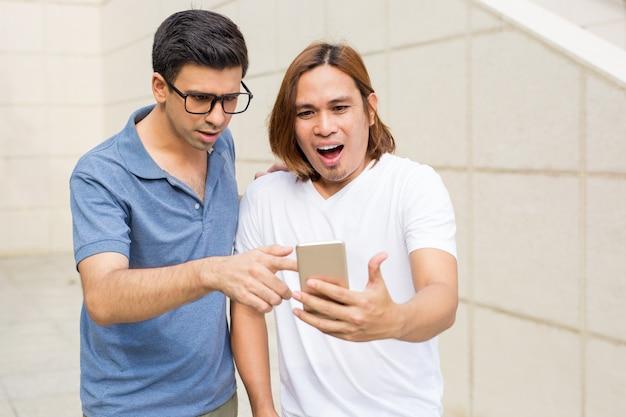 Deux hommes surpris utilisant smartphone outdoors