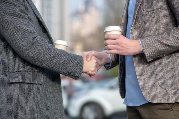 Deux hommes avec des tasses de café se serrant la main lors d'une réunion dans la rue
