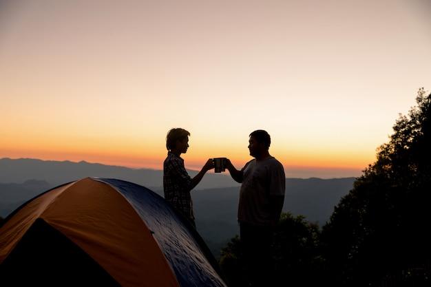 Deux hommes touristes heureux au sommet de la montagne près du feu de camp