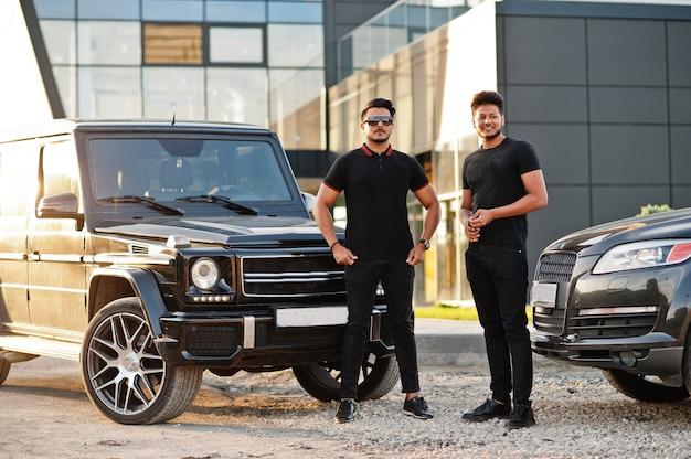 Deux hommes vêtus de noir posant près de voitures suv