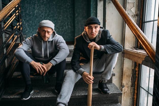 Deux hommes voleurs sont assis sur les escaliers