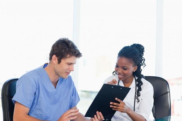 Deux infirmières travaillant sur un presse-papiers professionnel dans une pièce lumineuse