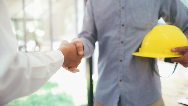 Deux ingénieur civil ou architecte ont une poignée de main dans le projet mega deal.