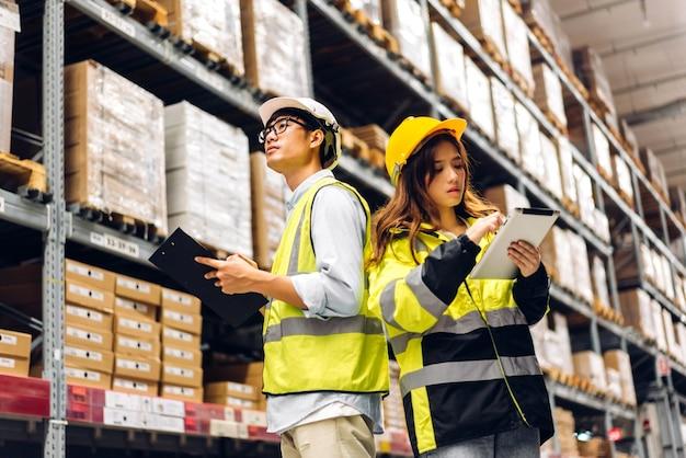 Deux ingénieurs asiatiques en équipe de casques commandent des détails sur une tablette pour vérifier les marchandises et les fournitures