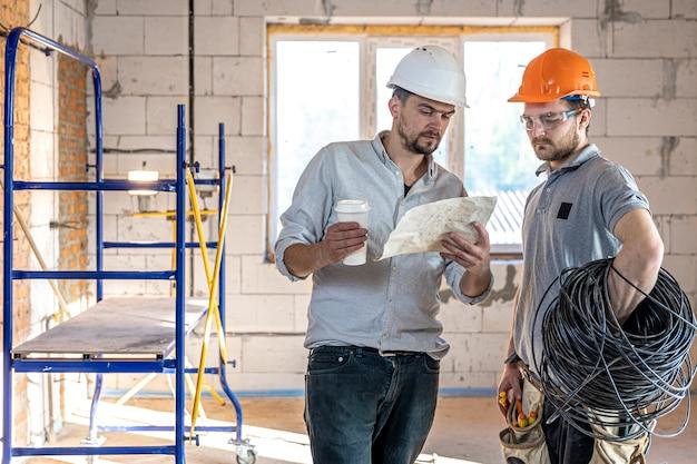 Deux ingénieurs constructeurs parlant au chantier, ingénieur expliquant un dessin à un ouvrier