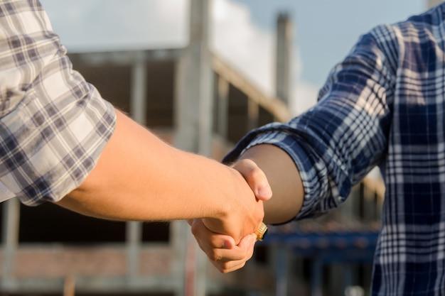 Deux ingénieurs en construction se serrant la main sur un chantier de construction