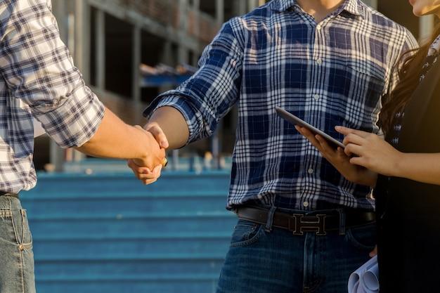 Deux ingénieurs en construction se serrant la main sur un chantier et une secrétaire au travail