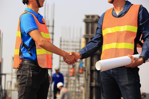 Deux ingénieurs en construction se serrent la main sur le chantier