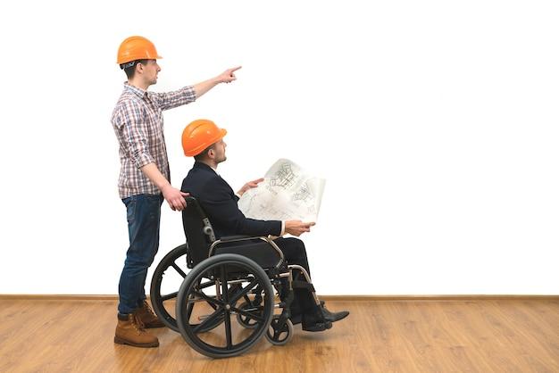Les deux ingénieurs avec un geste de fauteuil roulant sur le fond de mur blanc