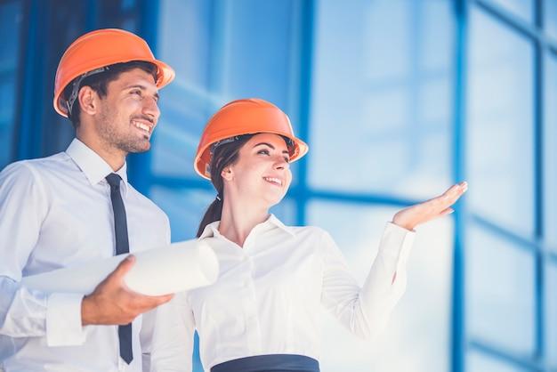 Les deux ingénieurs avec un geste de papier sur le fond du bâtiment moderne